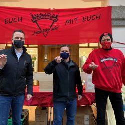 Dennis Berger und Andre Volke stehen zusammen mit Hajo - dem Wolfenbütteler Weihnachtsmarkt Standbetreiber Hajo vor seinem Stand und halten den Solidaritätspin hoch